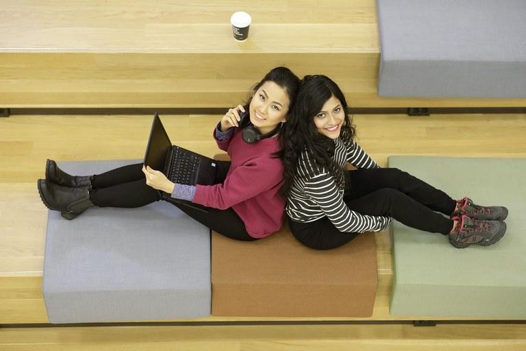 Kaksi nuorta naista istuu tietokoneen ja kahvikupin kanssa